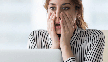 Business woman shocked at computer Featured