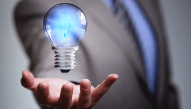 Idea Lightbulb Floating Above Hand Featured