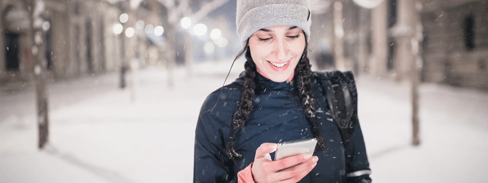 Woman using cell phone outside in snow