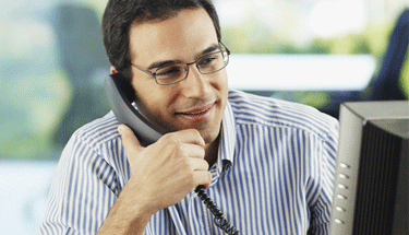Business man using a phone and computer Featured