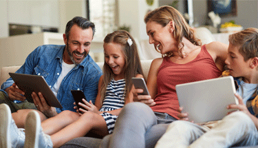 Family of four using technology on couch Featured