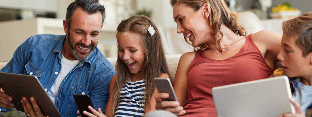 Family of four using technology on couch
