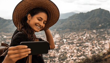 Woman taking a selfie and traveling Featured