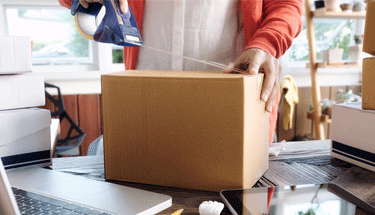 Man taping a package to sell Featured