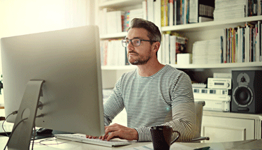Man working from home on a desktop computer Featured