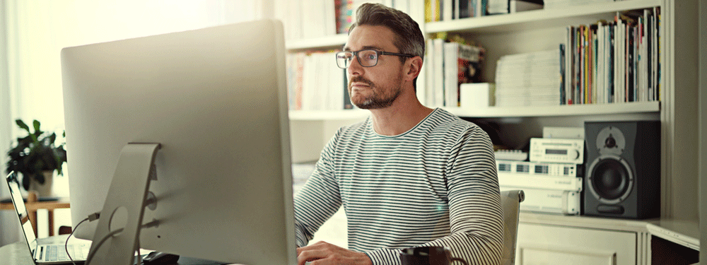 Man working from home on a desktop computer