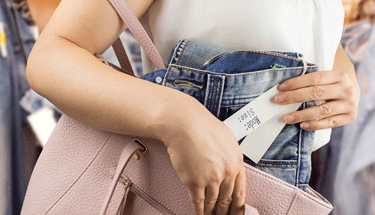 Woman shoplifting jeans Featured