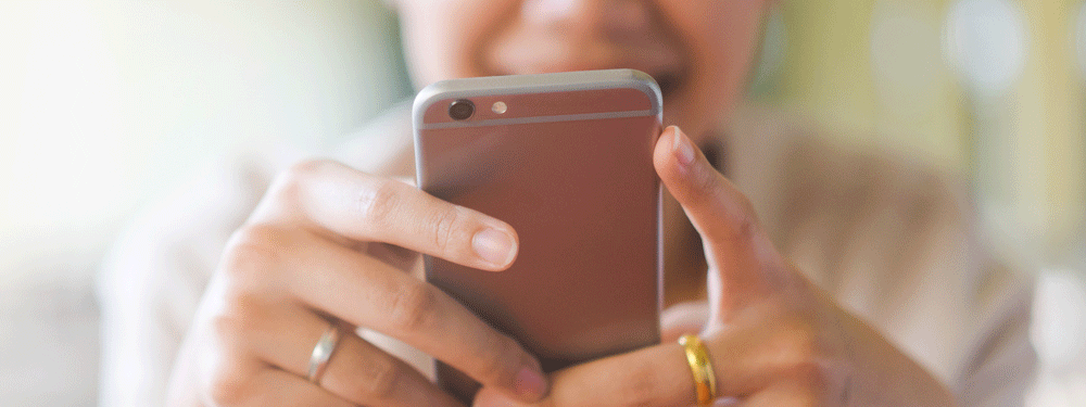 Woman using a rose gold smart phone