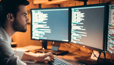 Man looking at coding on a desktop computer Featured