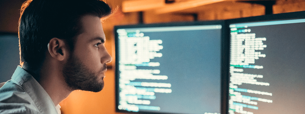 Man looking at coding on a desktop computer