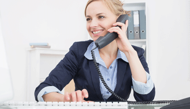 Business woman using a computer while on the phone Featured