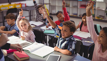 Children in a classroom raising their hands Featured