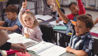 Children raising hands in school Featured