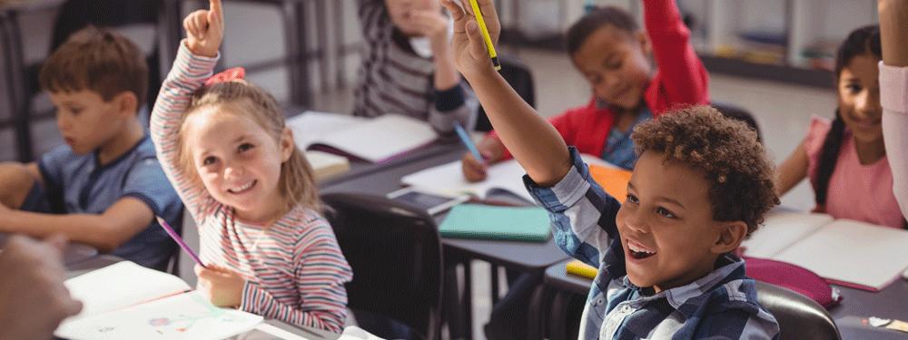 Children raising hands in school