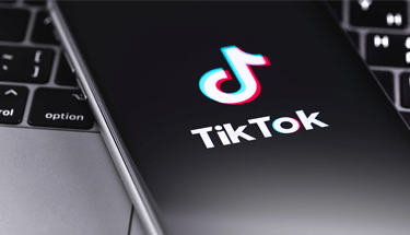 TikTok on cellphone on laptop Featured