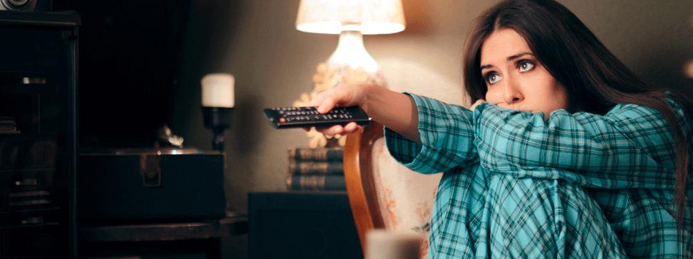 Woman binge watching TV in her pajamas
