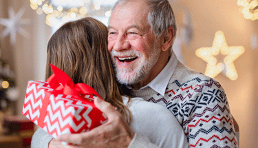 Happy elderly man with a gift hugging Featured