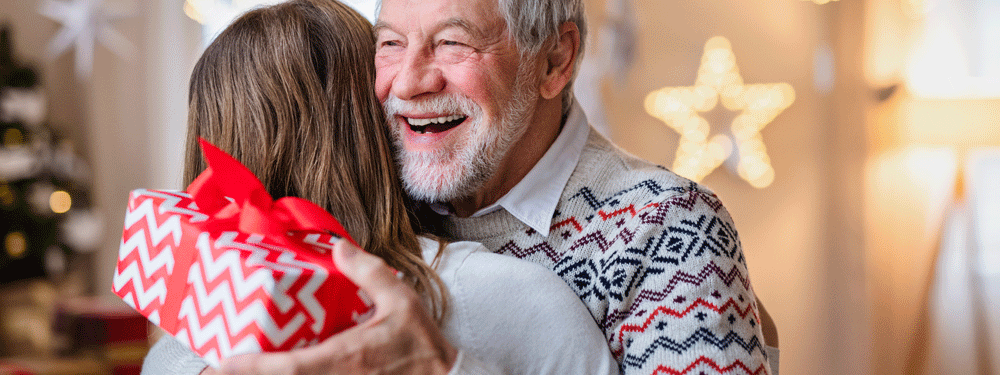 Happy elderly man with a gift hugging