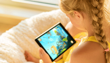 Young girl playing on a tablet Featured