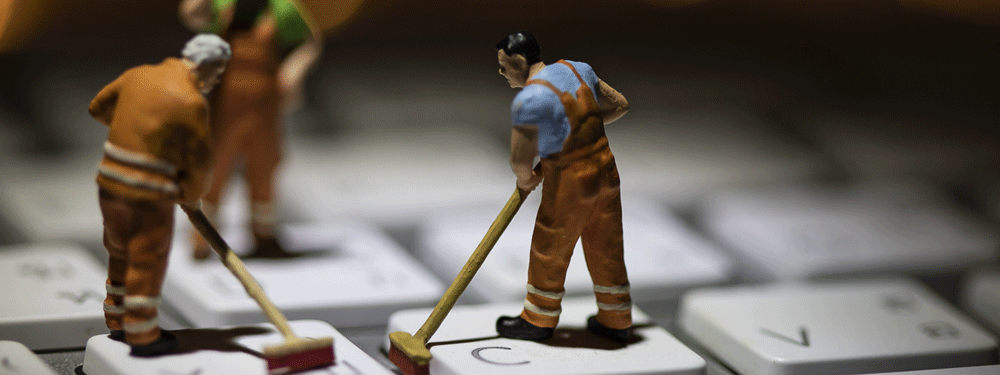 Man figurines cleaning a keyboard