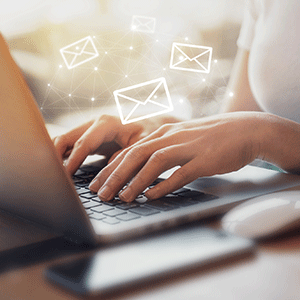 Business woman using laptop with floating mail logos
