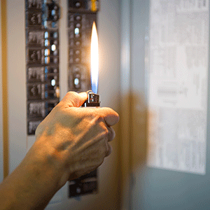 Man fixing a power outage holding a lighter with a large flame