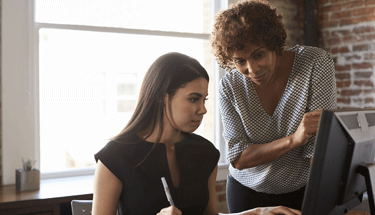 Woman working with boss on computer featured image