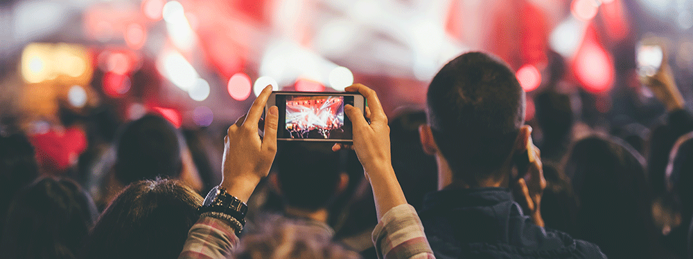 Person recording a concert video on cell phone