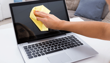 Woman cleaning laptop with yellow cloth and you can see her reflection