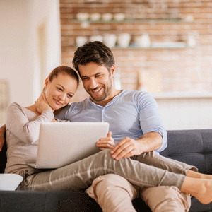 Couple on couch smiling and looking at laptop