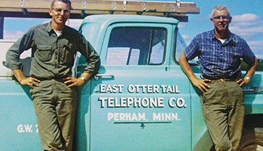 Two men standing in front of a East Ottertail Telephone Co. truck Featured
