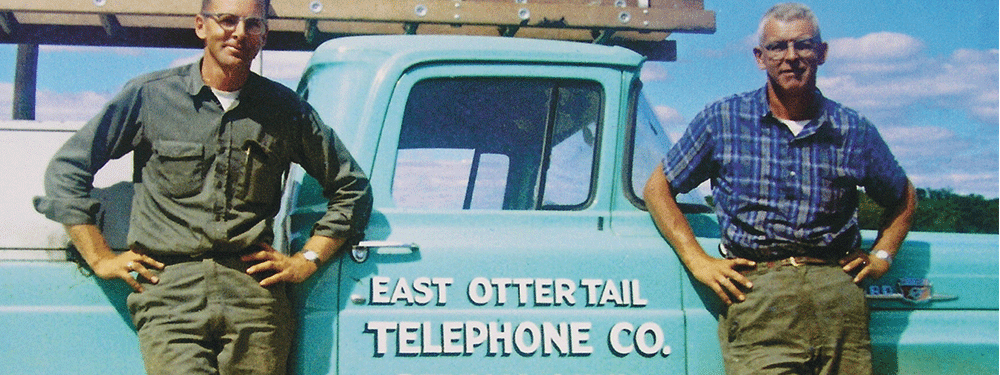 Two men standing in front of a East Ottertail Telephone Co. truck