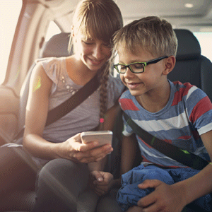 Little girl and little boy using cell phone in car