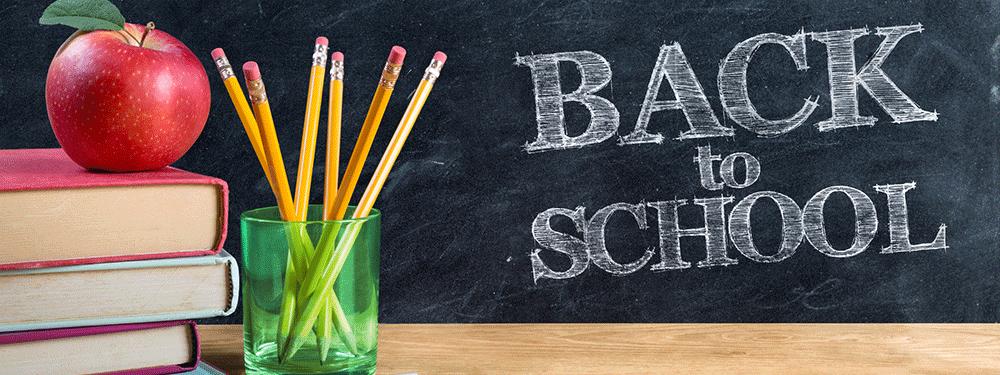 Back to school written in chalk on a chalkboard behind a desk