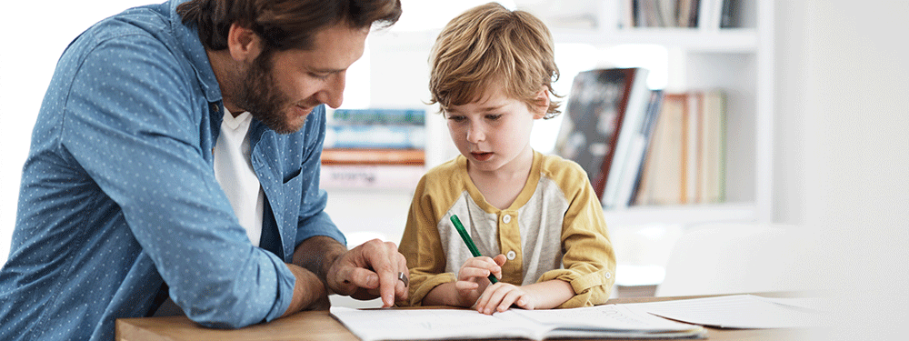 Dad helping his son with homework at a table