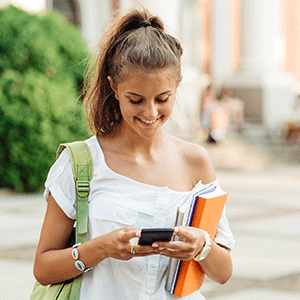 Girl using her cell phone and carrying books