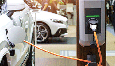 Electric Vehicle Plugged in Featured