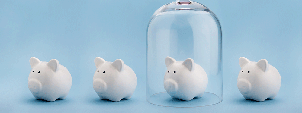 Four piggy banks and one is under a glass dome