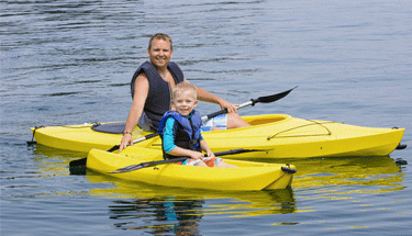 Father and son in kayaks on the water Featured