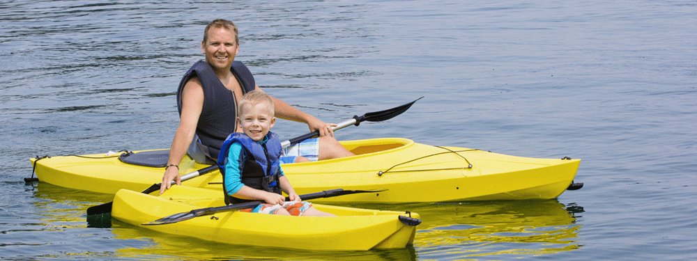 Father and son in kayaks on the water
