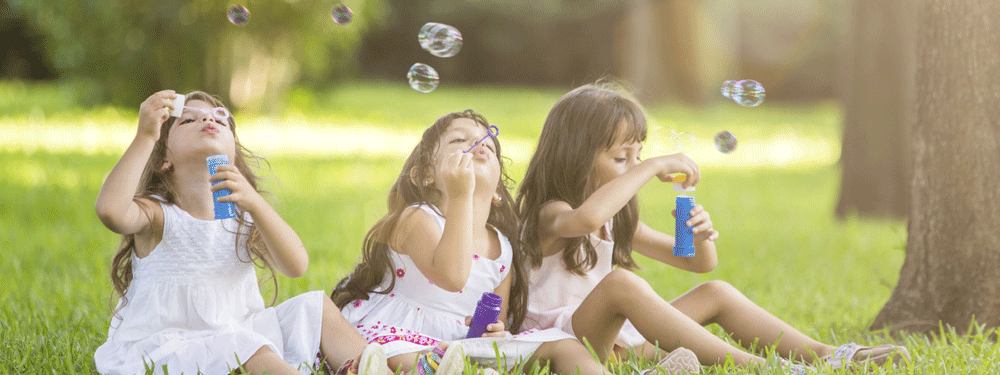 Three girls blowing bubbles outside
