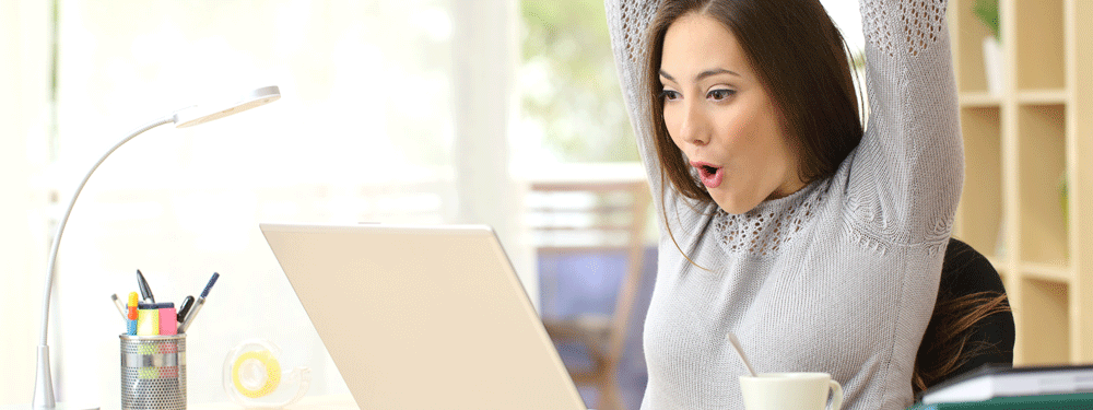 Woman excited on laptop