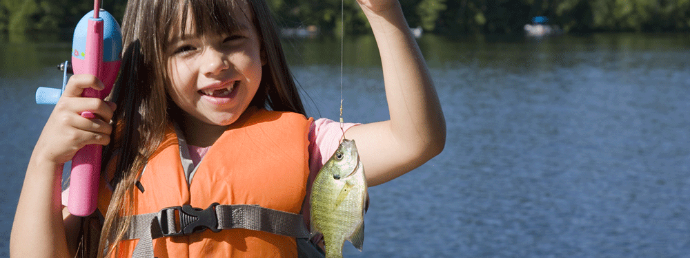 Little girl holding up a fish on a hook