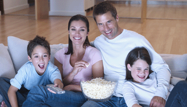 Family of four watching TV on the couch Featured