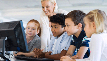 Students and a teacher working on a computer