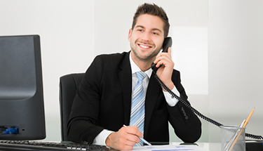 Man in black suit smiling on Hosted PBX phone and desktop computer
