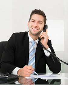 Man in black suit smiling on Hosted PBX phone