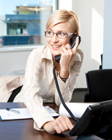 Happy woman looking away from Hosted PBX phone