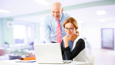 Man and woman working together on laptop in large office