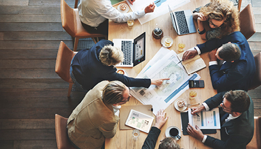 Large group of six coworkers brainstorming at table with maps